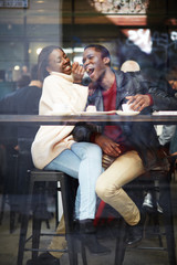 Laughing young couple in cafe, having a great time together