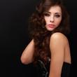 Beautiful makeup woman posing with long curly hair. Closeup