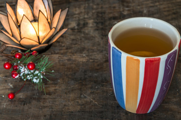 A cup of hot tea with lemon on rustic wooden table, close-up