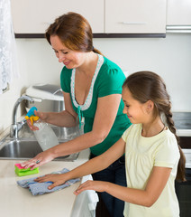 Little girl helping mother at kitchen