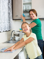 Mother with daughter cleaning at kitchen