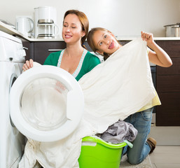 Woman with daughter near washing machine