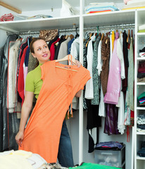 Housewife arranging clothes at wardrobe
