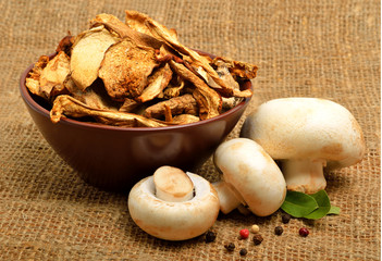 Dried mushrooms in the bawl, ceps and raw champignons on the sac