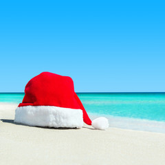 Red santa hat on white tropical beach sand - Christmas or New Ye
