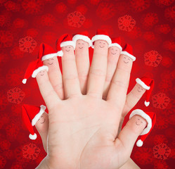 Fingers faces in Santa hats against red snowflakes background. C