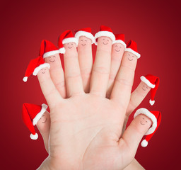 Fingers faces in Santa hats against red background. Concept for