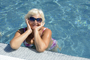 Aged woman on bright blue water of swimming pool background.