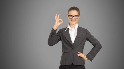 Young beautiful business woman showing copy space and showing ok