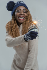 Beautiful african winter woman holding sparkler on gray backgrou