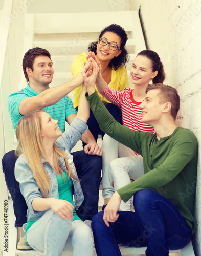 canvas print picture smiling students making high five gesture sitting