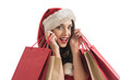 canvas print picture - Woman wearing Santa Claus hat with shopping bags