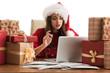 Woman wearing Santa Claus hat wrapping Christmas gift