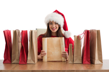 Lovely woman with shopping bags wearing Santa Claus hat dreaming