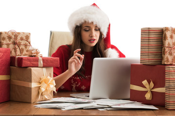 Woman wearing Santa Claus hat wrapping Christmas gift