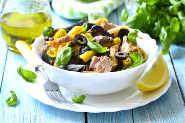 Salad from pasta and tuna with olives and basil.