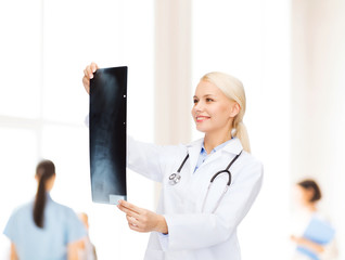 smiling female doctor looking at x-ray image