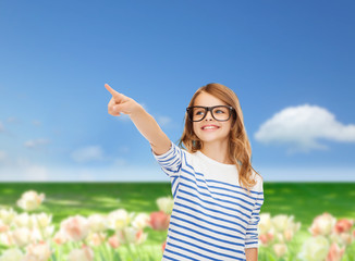 cute little girl in eyeglasses pointing in the air