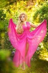 Woman dressed in pink gown walking in blooming garden