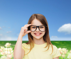 smiling cute little girl in black eyeglasses