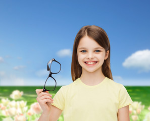 smiling cute little girl holding black eyeglasses