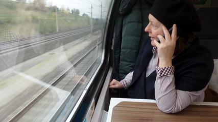 Frau telefoniert während Zugfahrt