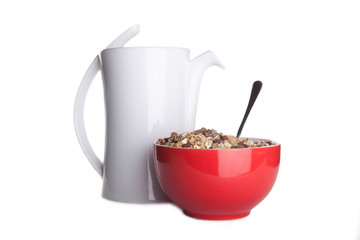 red dish with cereal and carafe of milk