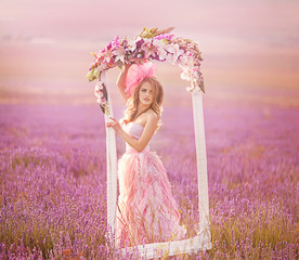 beautiful girl in a pink dress standing in a frame of flowers