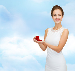 smiling woman holding red gift box with ring