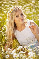 Beautiful woman enjoying daisy field