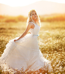 beautiful girl in a wedding dress in a field of daisies