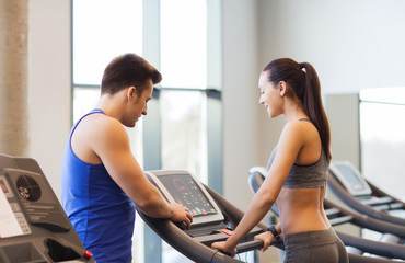 happy woman with trainer on treadmill in gym