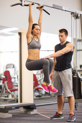 young woman with trainer doing leg raises in gym