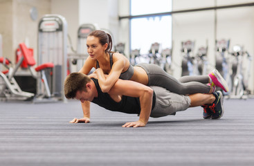 smiling couple doing push-ups in the gym
