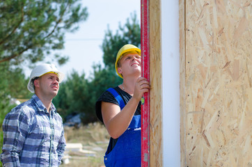 Two builders installing insulated wall panels