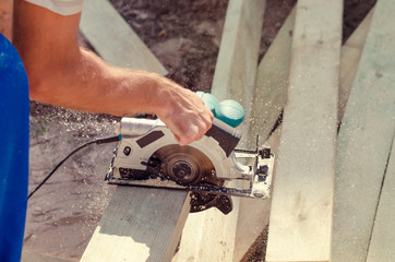 Workman cutting a wooden beam