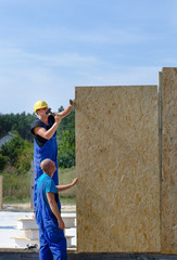Two builders installing wooden wall panels