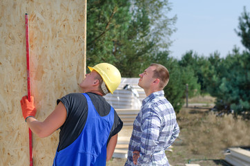 Builder and engineer checking a wooden wall panel