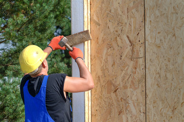 Builder hammering on a wooden wall panel