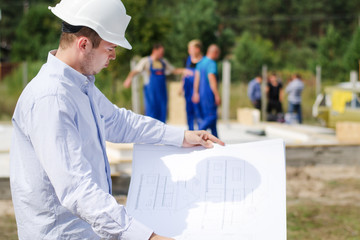 Architect or engineer checking plans on site