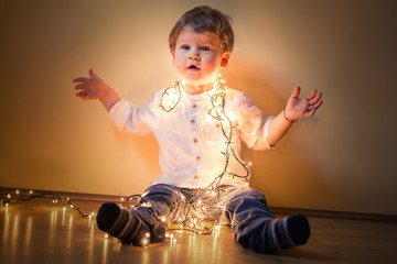 Happy boy playing with Christmas lights