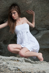 Portrait of a teen girl with white dress at the rocks