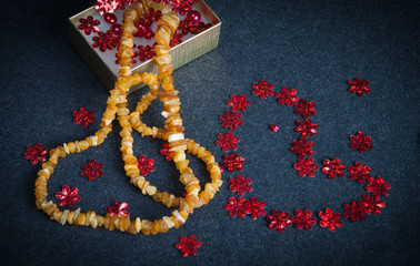Amber Necklace on Deep Grey Background with Bright Red Decoratio