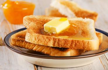 Slices toast bread fresh orange jam on a wooden background .