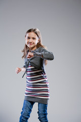 little girl dancing on a neutral background