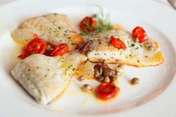 Fried fish fillet with capers and tomatoes