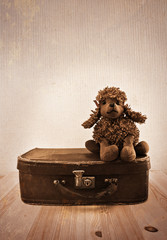 Old toy on a small road suitcase. Sepia toning.