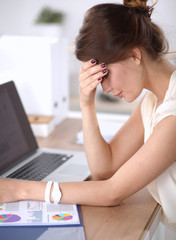 Portrait of tired young business woman with laptop computer at