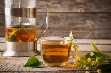 cup of tea with linden on wooden background