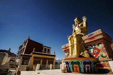 Golden Maitreya Buddha statue on blue sky